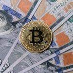 Criptomoeda Bitcoin sobre notas de Dólar dos Estados Unidos