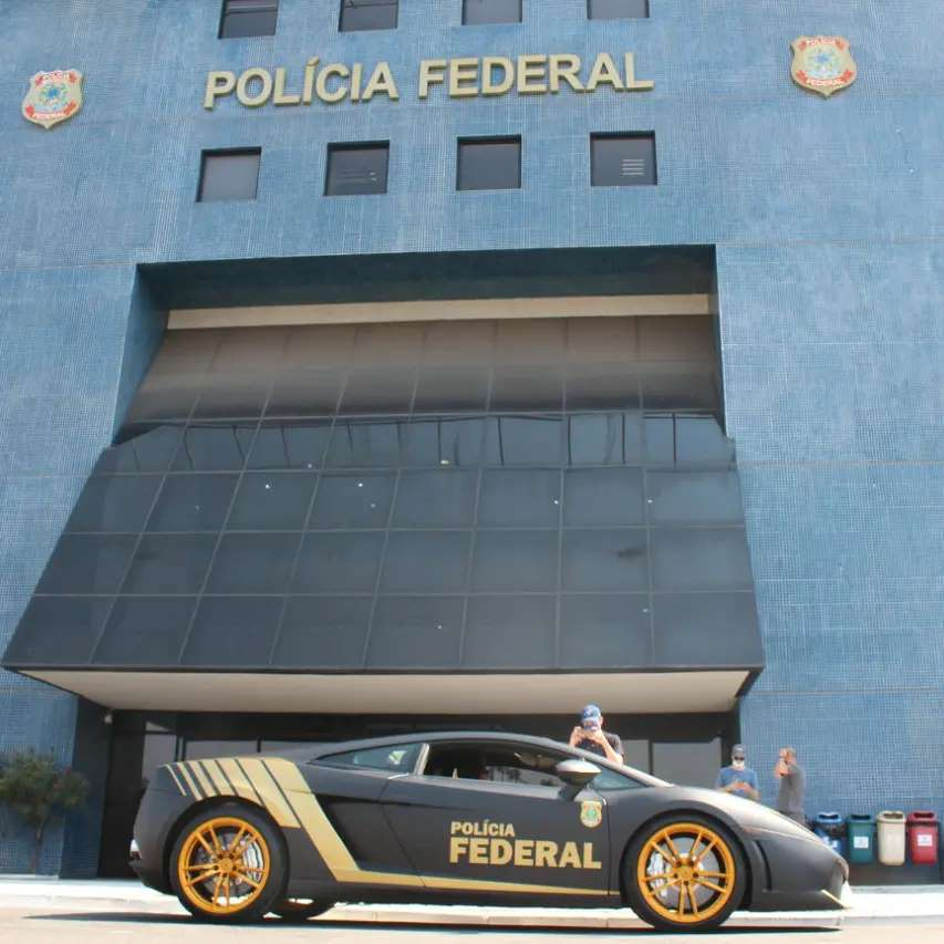 Foto de Agente da PF ao lado de nova viatura de luxo