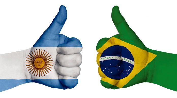 Mãos com bandeiras do Brasil e Argentina