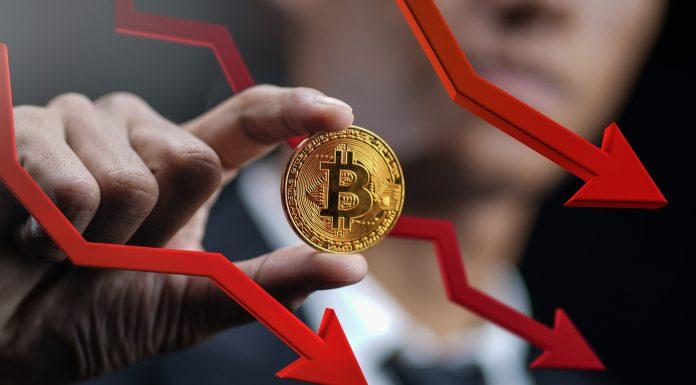 Trader segurando Bitcoin enquanto preço cai caindo queda despenca