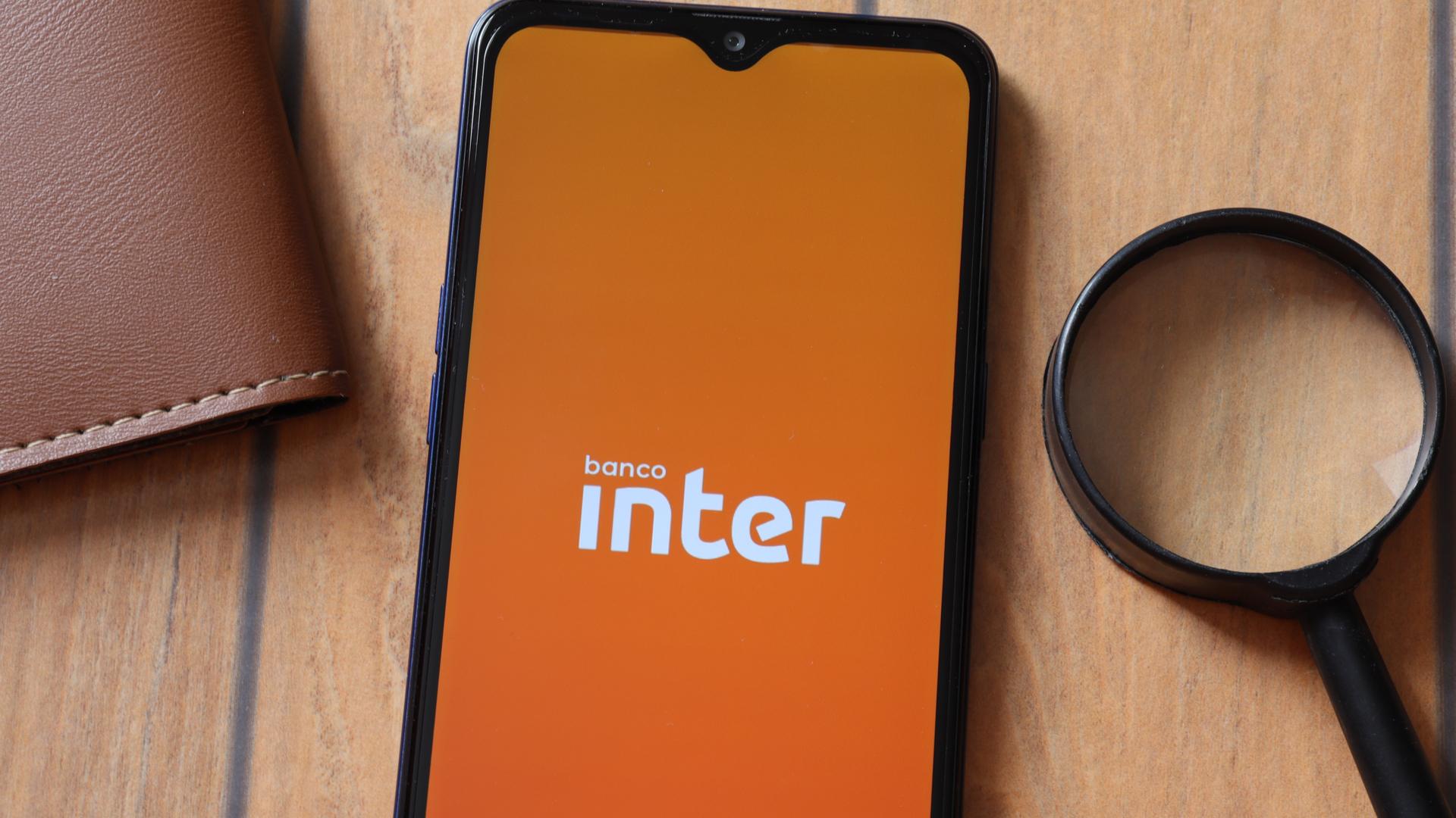 Banco Inter em tela de celular ao lado de lupa