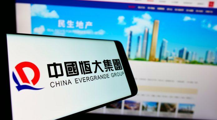 China Evergrande Group em tela de celular e computador Tether Bitcoin criptomoedas colapso crise