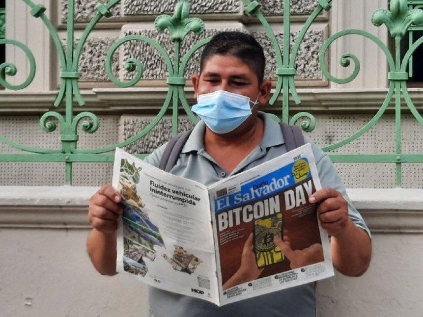 Homem lendo jornal com informação do Bitcoin em El Salvador
