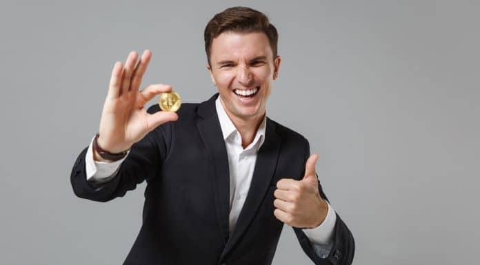 Homem segurando o Bitcoin e rindo