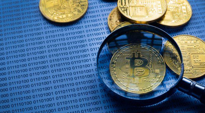Lupa mostrando Bitcoin em cima de papel com código binário rastreio rastrear procurar vasculhar