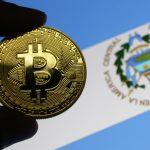 Mão segurando Bitcoin com bandeira de El Salvador