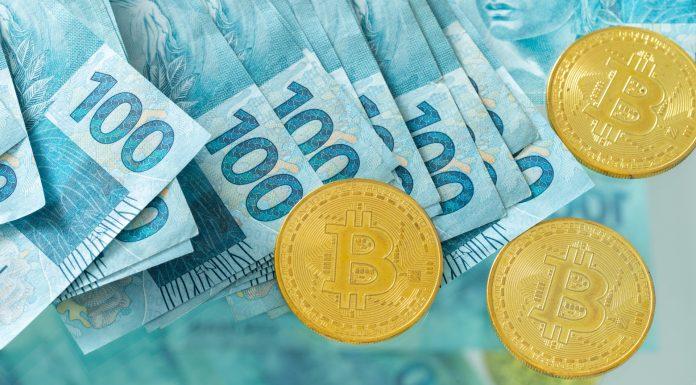 Notas de 100 reais e moedas de Bitcoin Brasil brasileiros