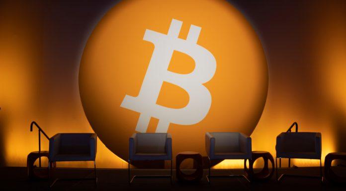 Palco com destaque a cadeiras e Bitcoin ao fundo Elon