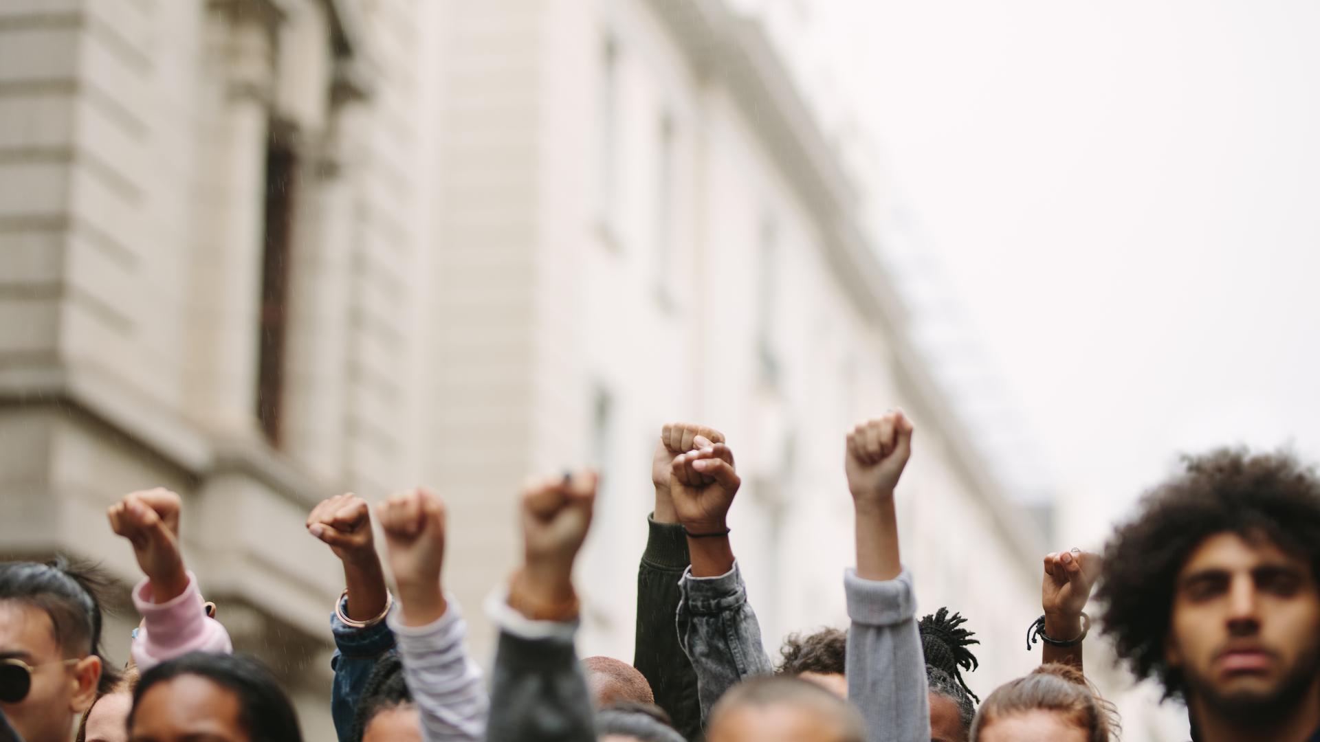 Punhos de grupo de manifestantes erguidos no ar